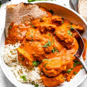 A bowl of chicken tikka masala with rice and naan