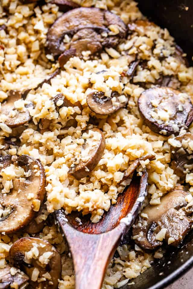 cooking and stirring cauliflower rice and sliced mushrooms