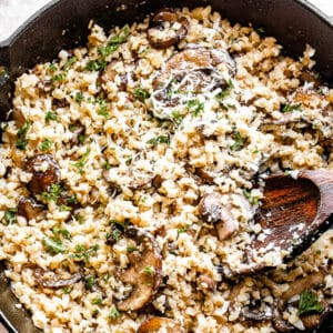 top view of a skillet filled with cauliflower rice and mushrooms topped with asiago cheese