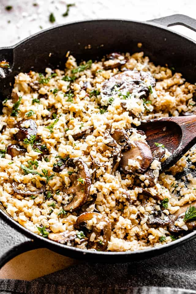 mixing cauliflower rice with wooden spoon inside a skillet