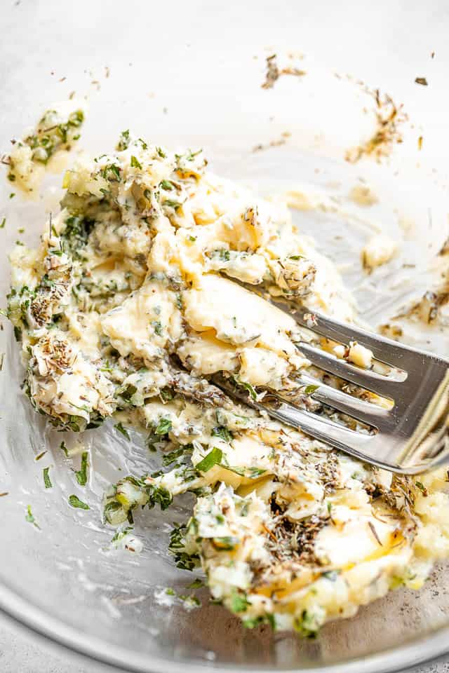 using a fork and mashing a garlic herb compound butter