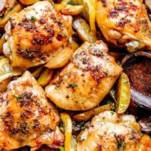 baked chicken thighs in a pan with potatoes and lemon slices