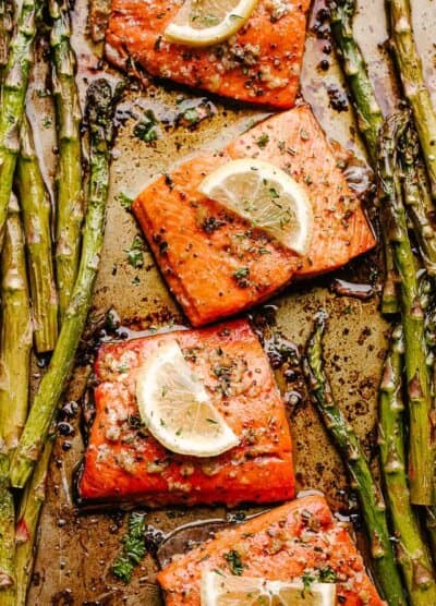 roasted sockeye salmon fillets topped with lemon slices and asparagus spears on either side
