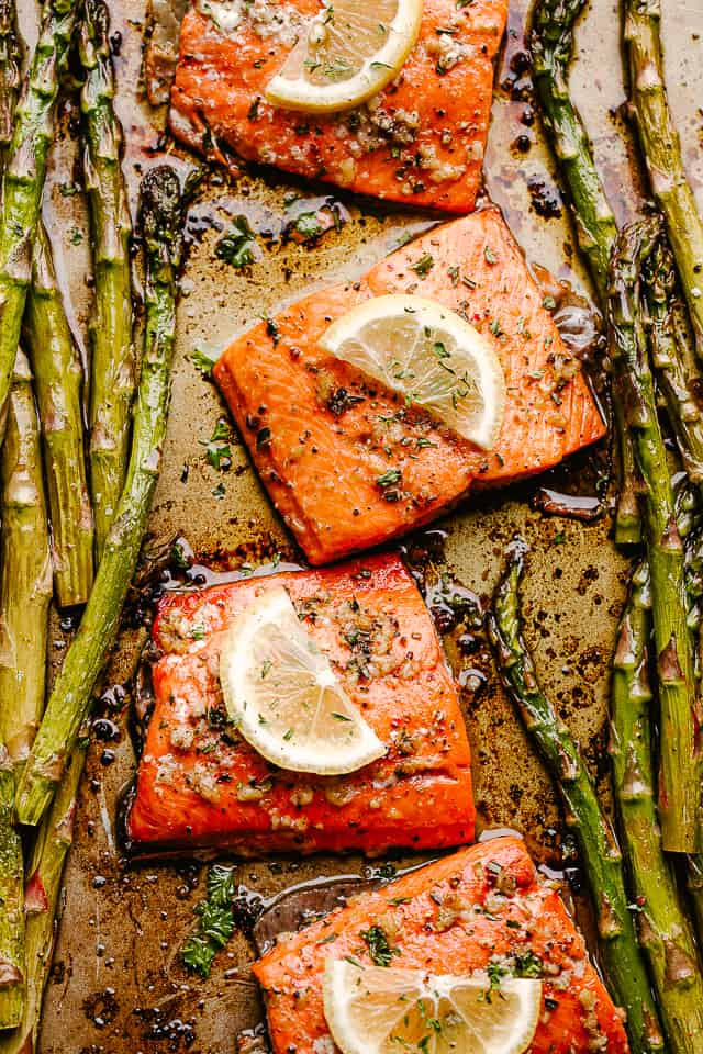 baked salmon fillets topped with lemon slices and asparagus spears on either side