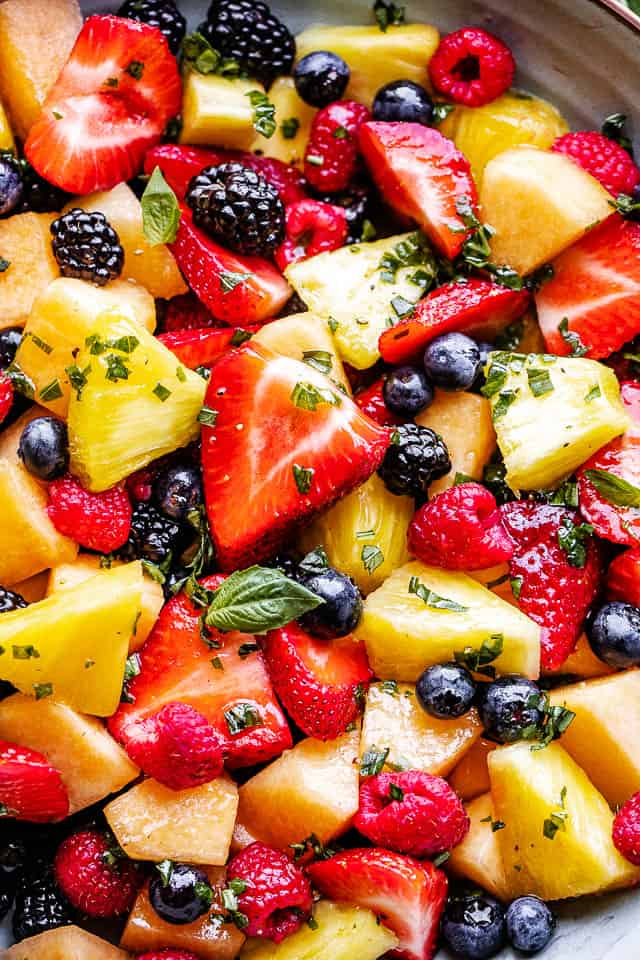 Close up photo of melon, strawberries, blackberries and pineapple in a fruit salad