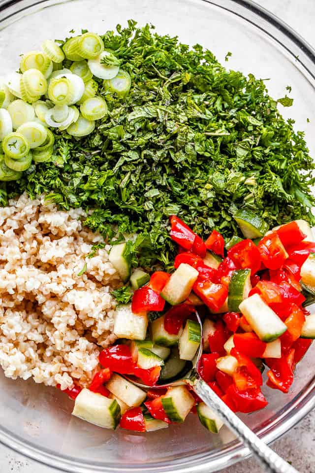 parsley, green onions, tomatoes, and bulgur for tabbouleh salad arranged in a glass bowl