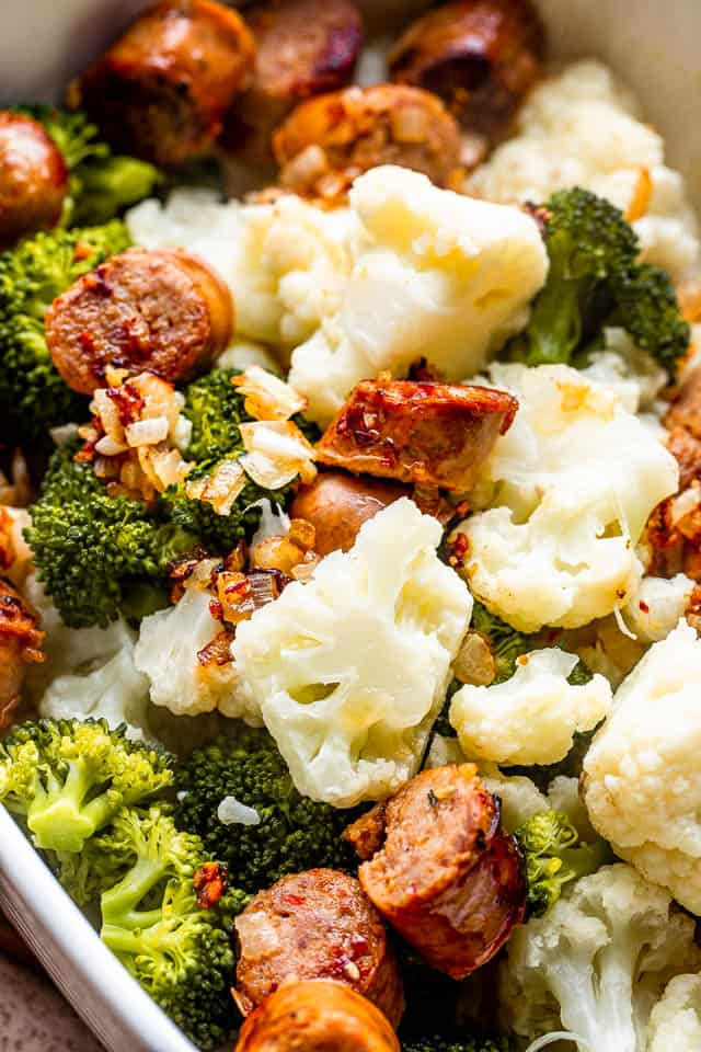 a mix of smoked sausage, cauliflower, and broccoli florets in a baking dish