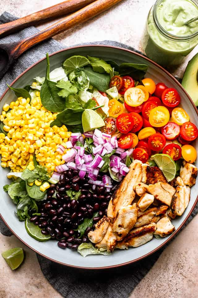 jar of salad dressing and two wooden spoons set next to a salad bowl filled with chicken strips, corn, tomatoes, onions, and black beans
