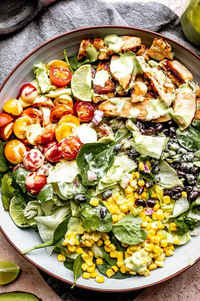 chicken strips, corn, tomatoes, and black beans set over salad greens in a salad bowl and drizzled with avocado salad dressing
