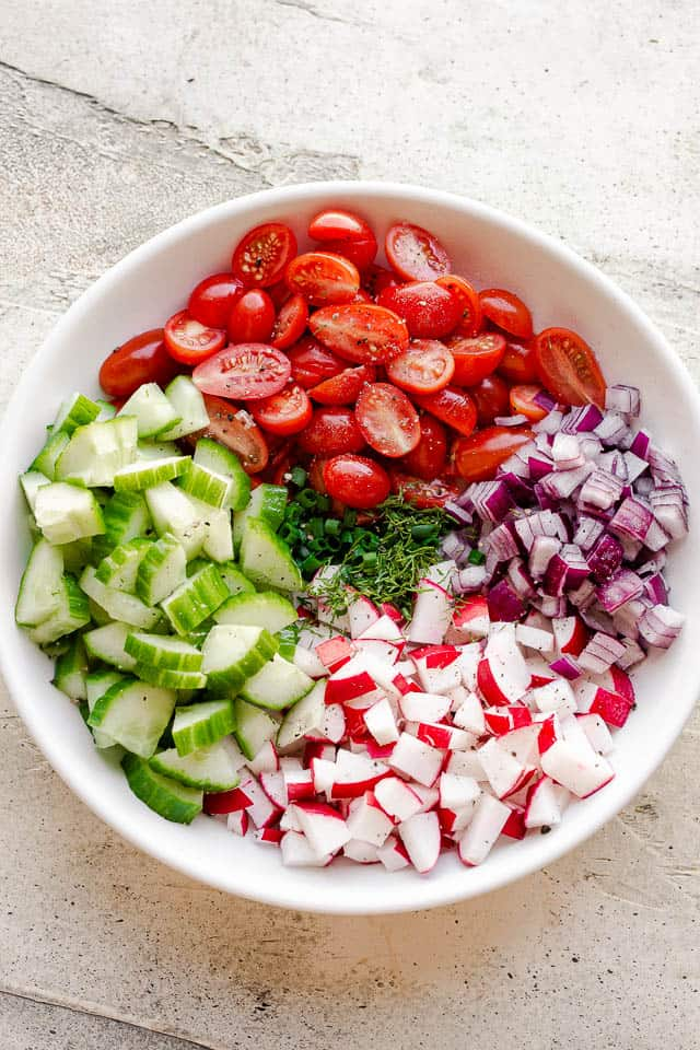 chopped red onions, cucumbers, tomatoes, radishes, and herbs in a bowl