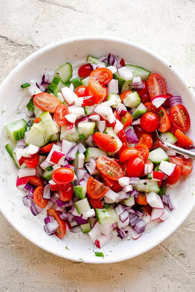 a mound of chopped cucumbers, tomatoes, and radishes inside of a white bowl