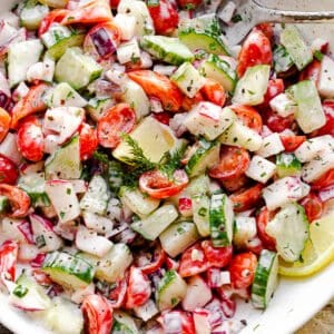 top view of a silver spoon inside a white salad bowl filled with chopped tomatoes, cucumbers, radishes, herbs, and tossed with a creamy dressing