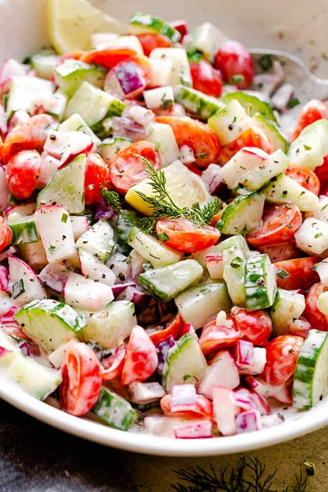 side view of a creamy salad with tomatoes, cucumbers, and radishes