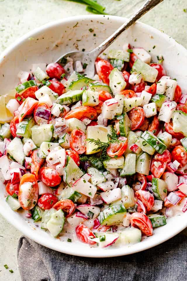 large silver spoon inside a white bowl with chopped cucumbers, chopped tomatoes, and chopped radishes