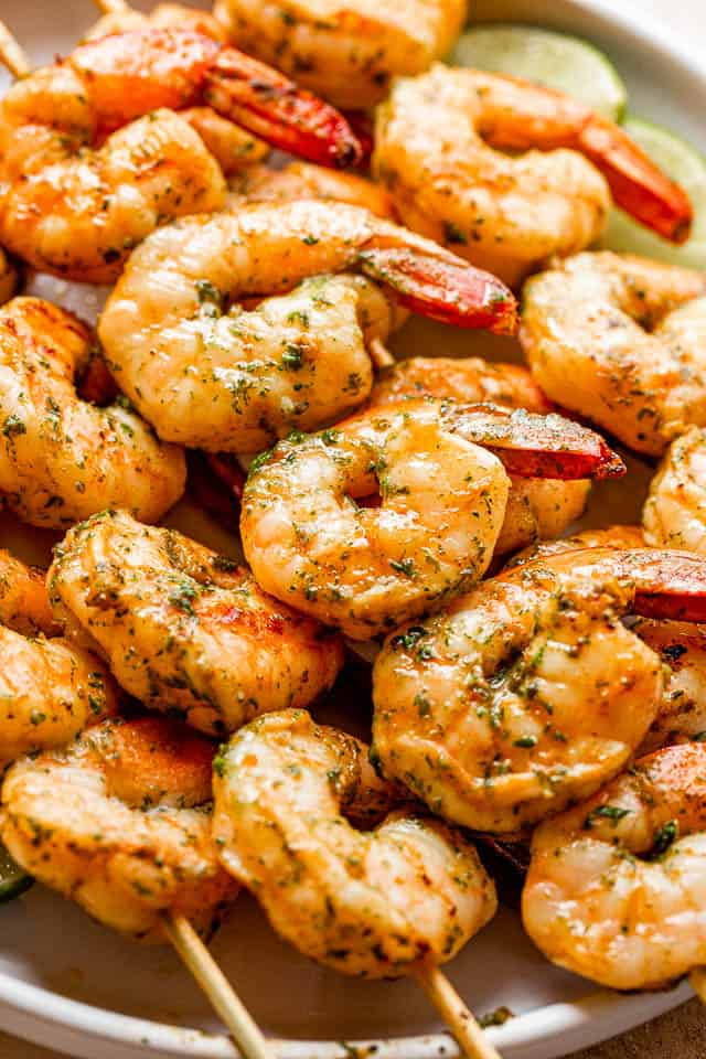 grilled shrimp on skewers stacked on a plate