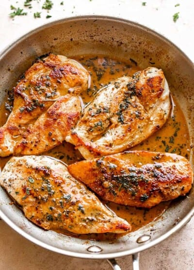 four chicken breasts cooking in a stainless steel skillet