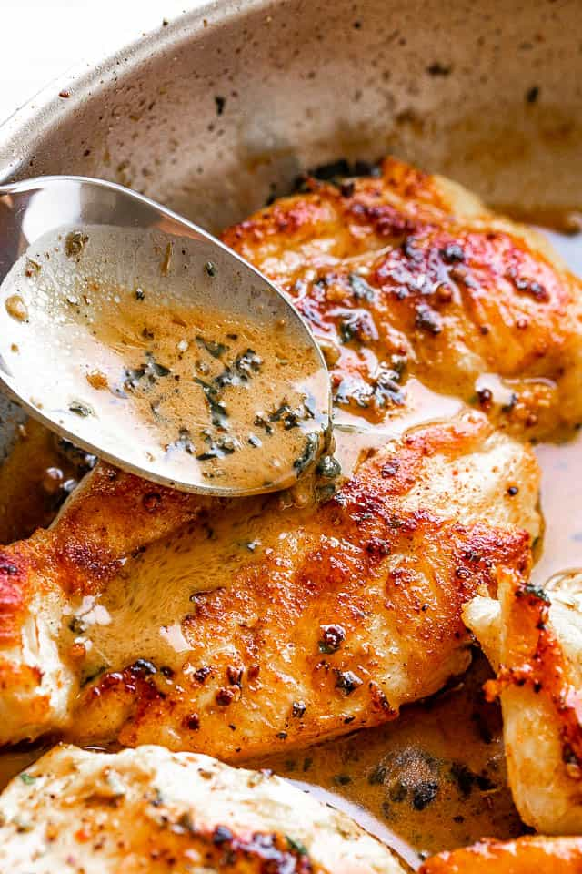 pouring butter and herb sauce over pan fried chicken