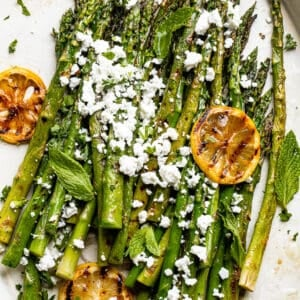 serving grilled asparagus with feta on an oval plate