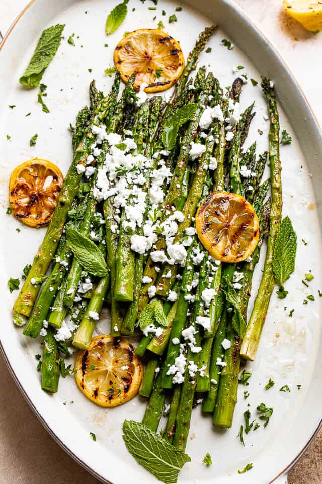 oval platter with grilled asparagus topped with feta cheese and lemon slices
