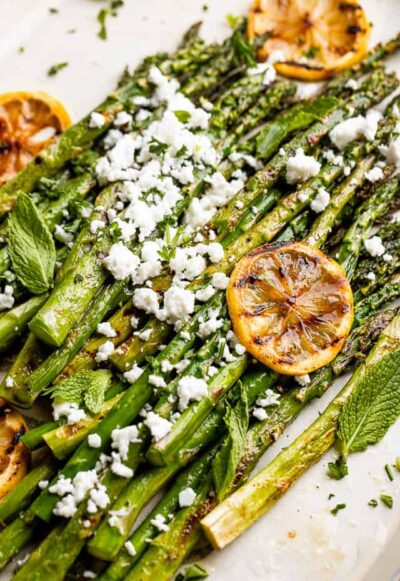 side close up shot of asparagus sprinkled with feta cheese and slices of lemon