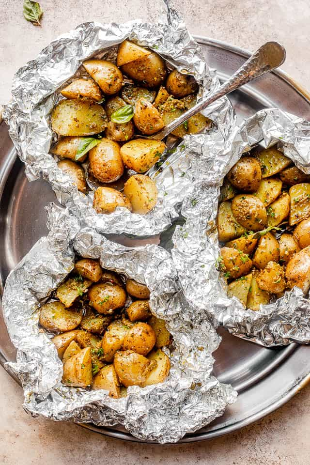 top view of a pewter plate with three foil packets filled with basil pesto brushed potatoes