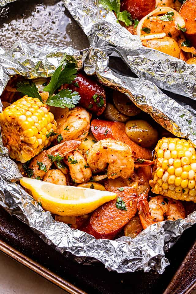 grilled shrimp with sausages and corn inside a foil and served with lemon wedges