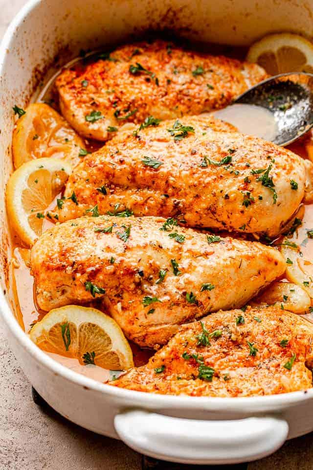 baked chicken breasts set over lemon slices in a baking dish