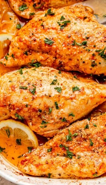 close up above view shot of baked chicken breasts in a white baking dish sprinkled with parsley and garnished with lemons