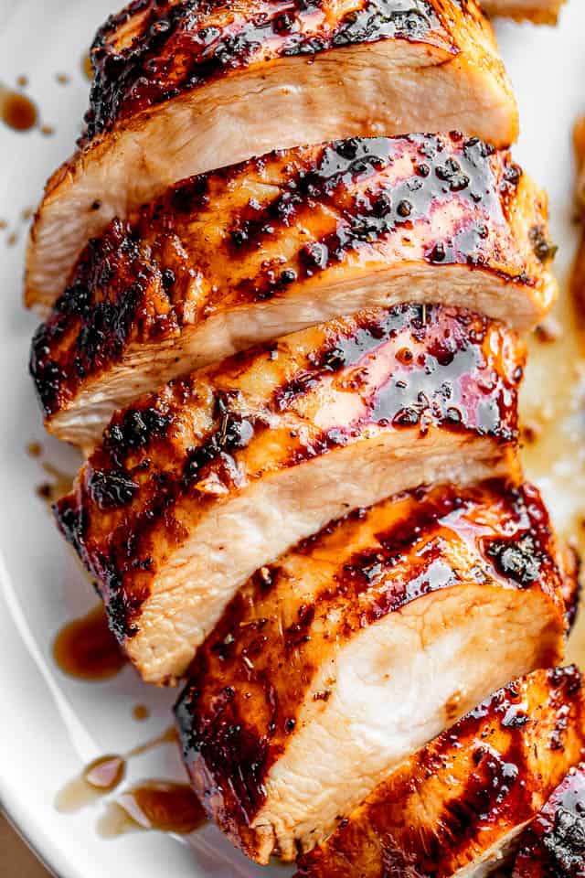 sliced chicken breast with grill marks set on a white plate