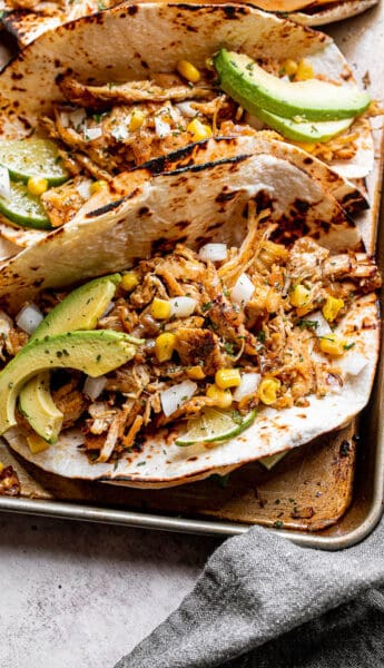 chicken carnitas tacos topped with avocado, onions, and corn