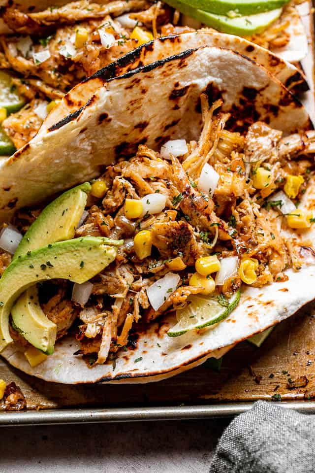 close up shot of a taco filled with chicken carnitas, avocado slices, corn, and onions