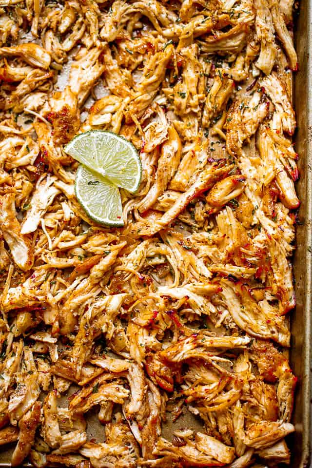 two lemon slices on top of shredded chicken carnitas spread on a baking sheet