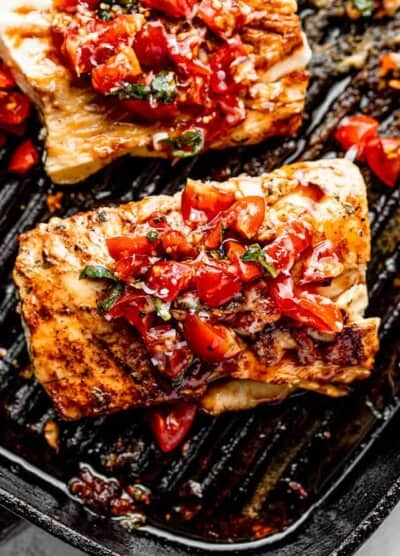 mahi mahi fish set on a black grill pan and topped with a tomato salad and fresh basil