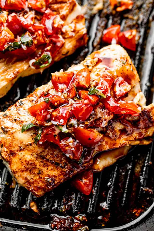 grilled mahi mahi steaks on a grill pan topped with a balsamic tomato salad