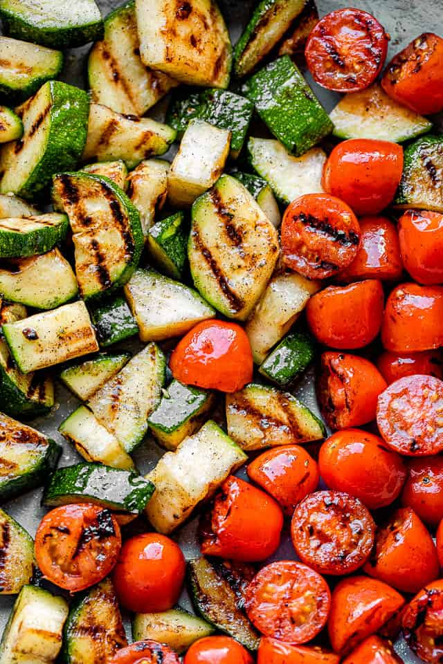 close up shot of grilled sliced zucchini and grilled cherry tomatoes