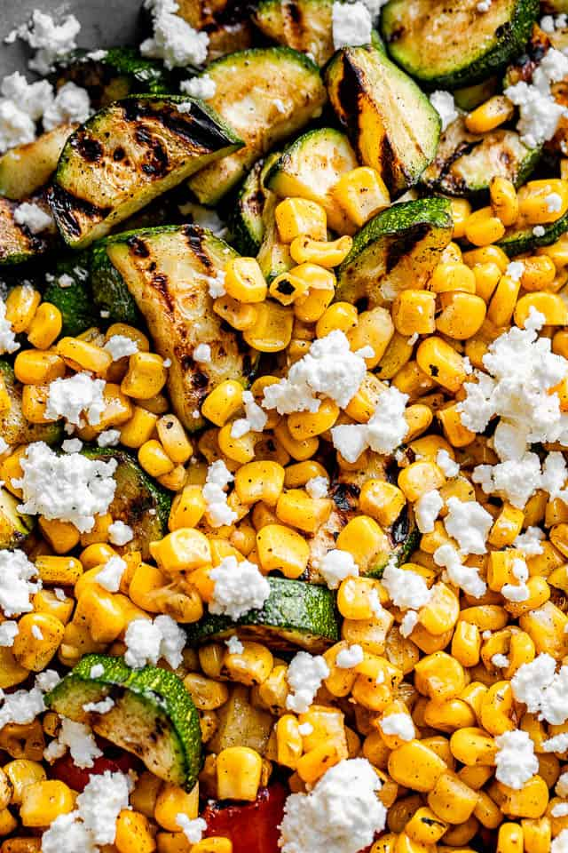 close up view of grilled zucchini topped with grilled corn and crumbled goat cheese