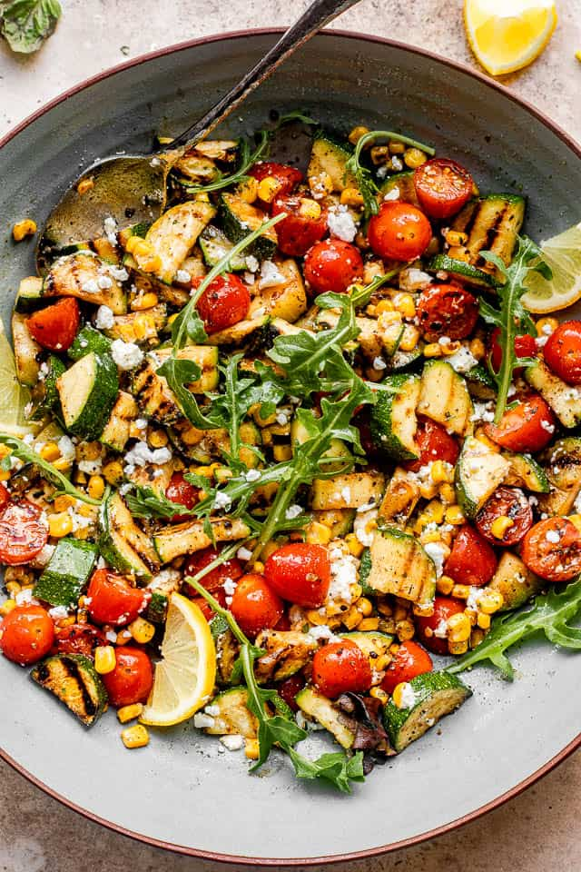top view of a large blue salad bowl filled with grilled zucchini slices, cherry tomatoes, and corn kernels