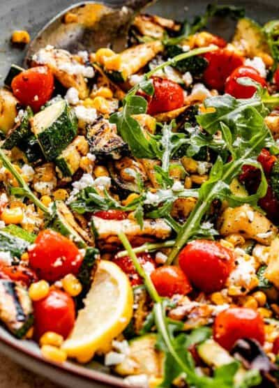 side shot of a blue salad bowl filled with grilled corn, tomatoes, zucchini, goat cheese, lemon slices, and arugula on top