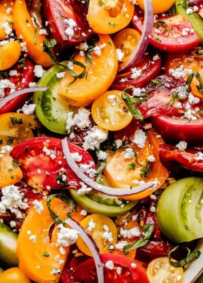 close up shot of wedges of colored tomatoes topped with slices of red onions and crumbled feta cheese