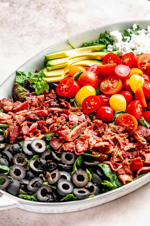 side shot of a salad plate with bacon, olives, tomatoes, cheese, avocado, and lettuce greens