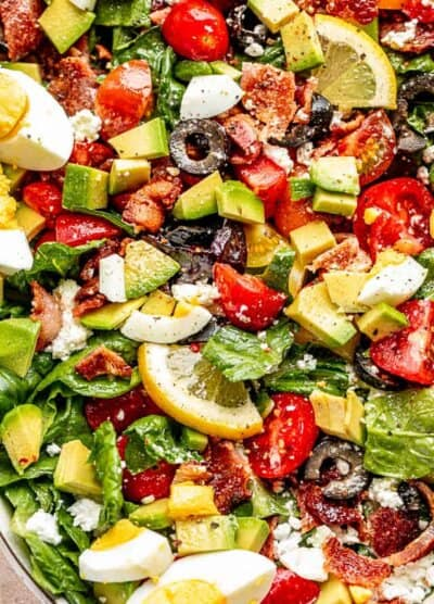 close up top view shot of boiled egg wedges, lemon slices, chopped avocados, tomatoes, and bacon set over leafy lettuce