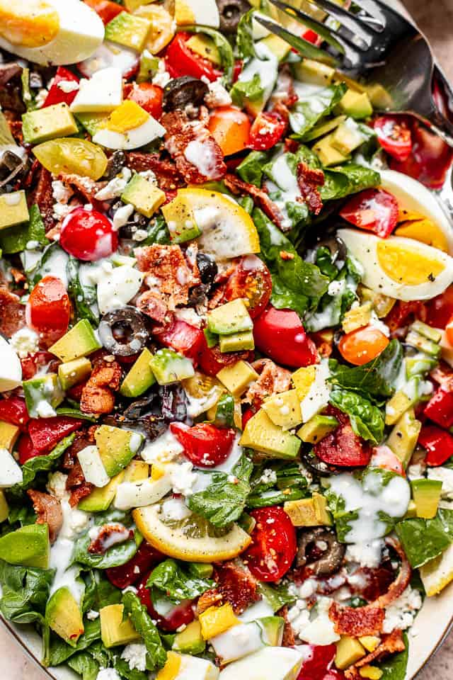 top view shot of boiled egg wedges, lemon slices, chopped avocados, tomatoes, and bacon set on top of baby spinach leaves and salad greens
