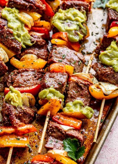 side view of grilled steak kabobs topped with guacamole