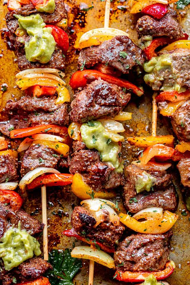close up shot of steak and vegetable kabobs set over a plate and topped with guacamole
