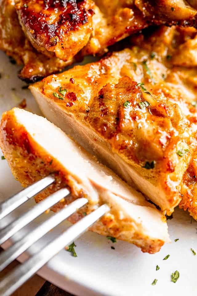 cutting a slice off cooked chicken thighs and holding it in place with a fork