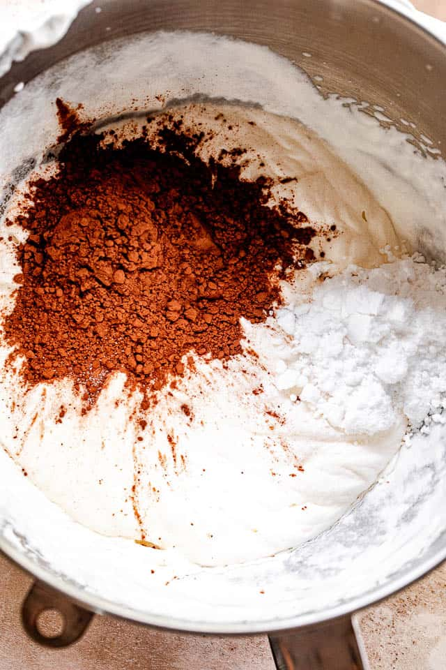 cocoa powder, heavy cream, and powdered sugar in a mixing bowl