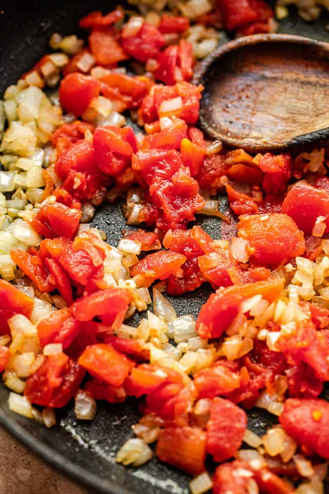 frying onions and diced tomatoes in a black skillet