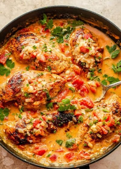 coconut milk chicken breasts in black skillet garnished with cilantro