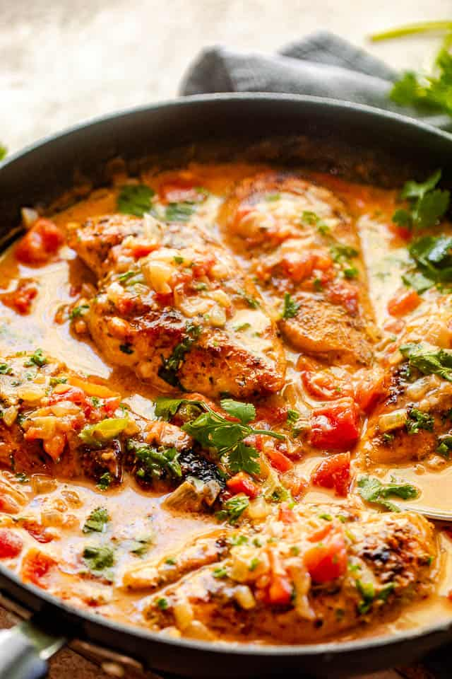 side view of chicken breasts in coconut milk sauce with diced tomatoes, onions, and cilantro