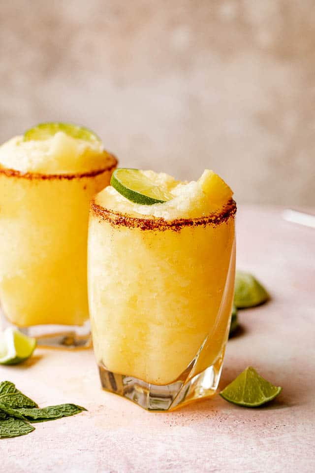 pineapple margaritas in cocktail glasses topped with sliced lime and pineapple chunks